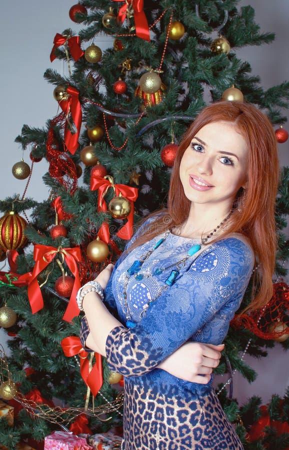 Όμορφη γυναίκα κοντά στο χριστουγεννιάτικο δέντρο στοκ εικόνα