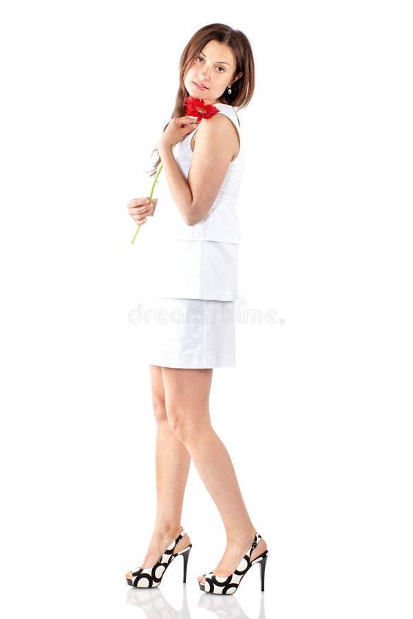 Όμορφη γυναίκα με μοντέρνο λευκό φόρεμα, με κόκκινο λουλούδι, που ποζάρει στο στούντιο σε λευκό φόντο στοκ φωτογραφία