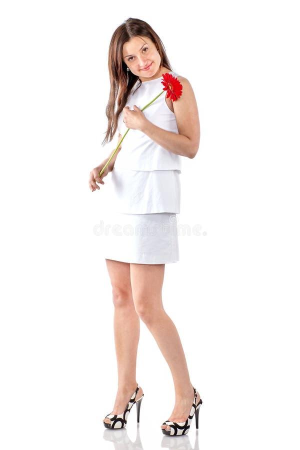 Όμορφη γυναίκα με μοντέρνο λευκό φόρεμα, με κόκκινο λουλούδι, που ποζάρει στο στούντιο σε λευκό φόντο στοκ εικόνα