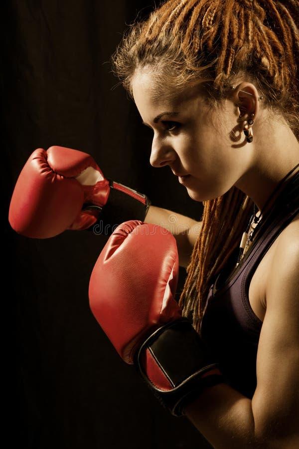 Όμορφη γυναίκα με τα κόκκινα εγκιβωτίζοντας γάντια, dreadlocks σε ένα μαύρο BA στοκ φωτογραφία