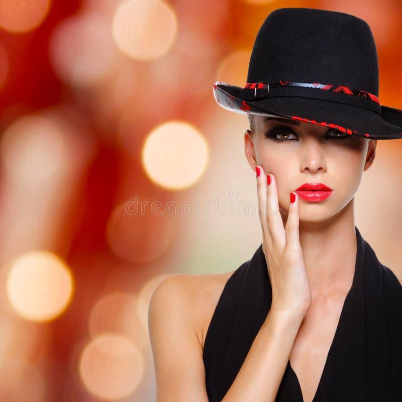 Όμορφη γυναίκα με τα κόκκινα χείλια και τα καρφιά στο μαύρο καπέλο στοκ φωτογραφία