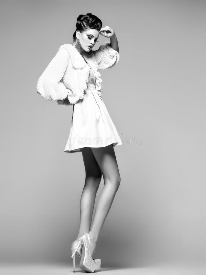 Όμορφη γυναίκα με τα μακριά πόδια στο άσπρα φόρεμα, τη γούνα και τα υψηλός-τακούνια που θέτουν στο στούντιο στοκ φωτογραφία