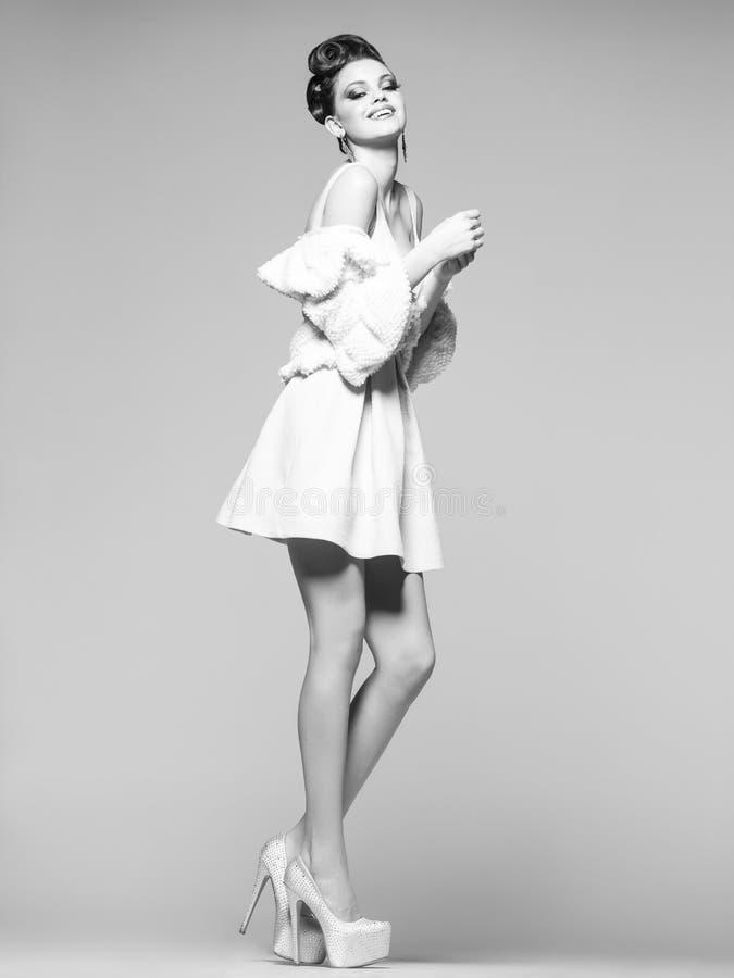 Όμορφη γυναίκα με τα μακριά πόδια στο άσπρα φόρεμα, τη γούνα και τα υψηλός-τακούνια στοκ φωτογραφία με δικαίωμα ελεύθερης χρήσης