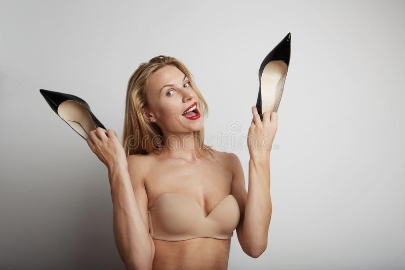 Όμορφη γυναίκα με τα παπούτσια στα χέρια της στοκ εικόνα με δικαίωμα ελεύθερης χρήσης