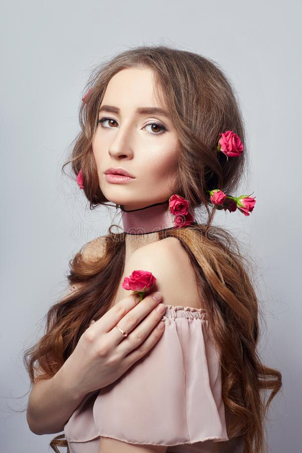 Όμορφη γυναίκα με τα ροδαλά λουλούδια σε την μακρυμάλλη, ένας επίδεσμος γύρω από το λαιμό της Καθαρό όμορφο δέρμα προσώπου, καλλυ στοκ εικόνα με δικαίωμα ελεύθερης χρήσης
