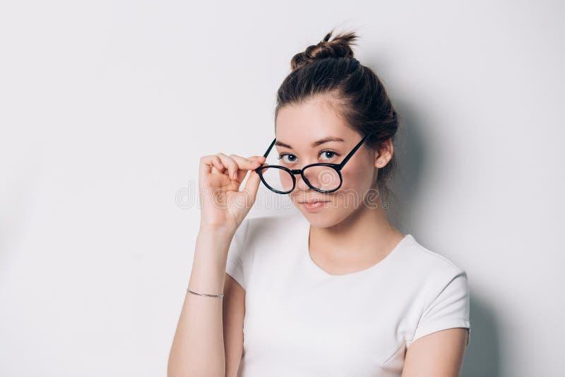 Όμορφη γυναίκα με τα στρογγυλά γυαλιά που εξετάζει τη κάμερα στο άσπρο υπόβαθρο στοκ εικόνα