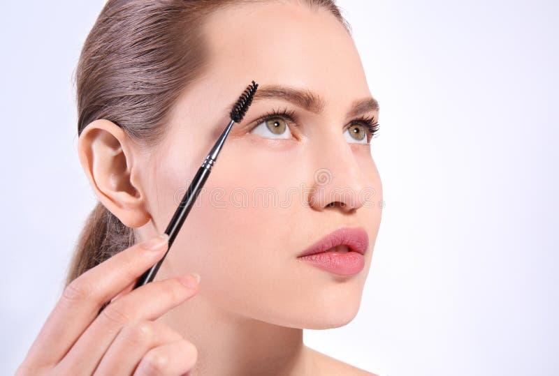 Όμορφη γυναίκα με τα τέλεια φρύδια που ισχύει makeup στοκ εικόνα