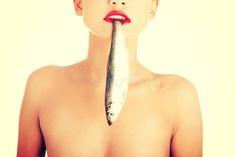 Όμορφη γυναίκα με τα ψάρια στο στόμα της στοκ εικόνες με δικαίωμα ελεύθερης χρήσης