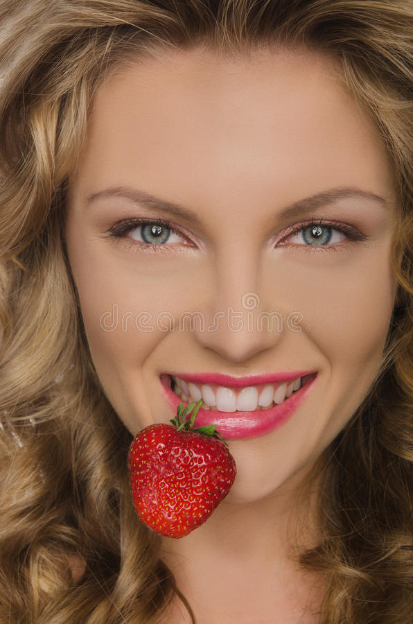 Όμορφη γυναίκα με τα δόντια φραουλών στοκ φωτογραφίες