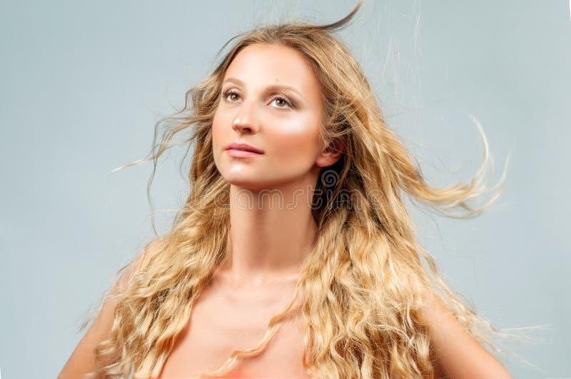 Όμορφη γυναίκα με την κυματιστή μακριά ξανθή τρίχα στοκ φωτογραφία