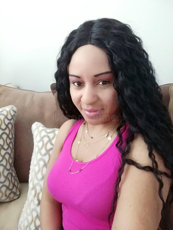 Όμορφη γυναίκα με την κυματιστή συνεδρίαση τρίχας σε έναν καναπέ στοκ φωτογραφία