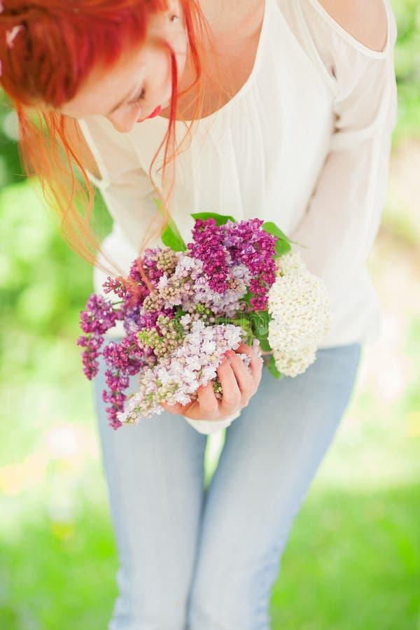 Όμορφη γυναίκα με την κόκκινη άσπρη και ιώδη ιώδη άνθιση εκμετάλλευσης τρίχας στα χέρια της, υπαίθριος κήπος στοκ εικόνα
