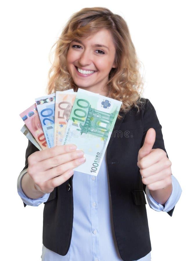 Όμορφη γυναίκα με την ξανθή τρίχα και χρήματα που παρουσιάζουν αντίχειρα στοκ εικόνες