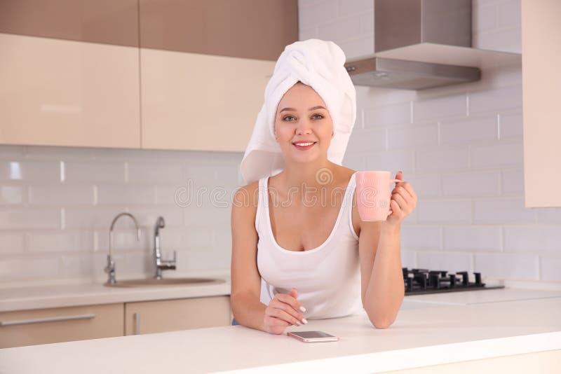 Όμορφη γυναίκα με την πετσέτα στο επικεφαλής τσάι κατανάλωσης και χρησιμοποίηση του smartphone στοκ φωτογραφία με δικαίωμα ελεύθερης χρήσης