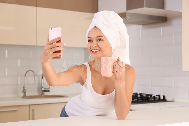 Όμορφη γυναίκα με την πετσέτα στο κεφάλι που παίρνει selfie στοκ φωτογραφία με δικαίωμα ελεύθερης χρήσης