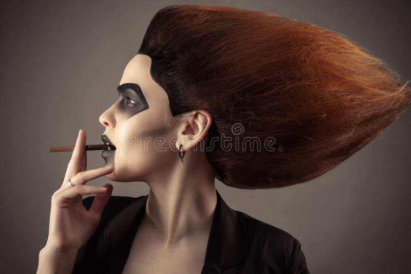 Όμορφη γυναίκα με την πολύβλαστη τρίχα με το τσιγάρο στο στόμα στοκ εικόνες