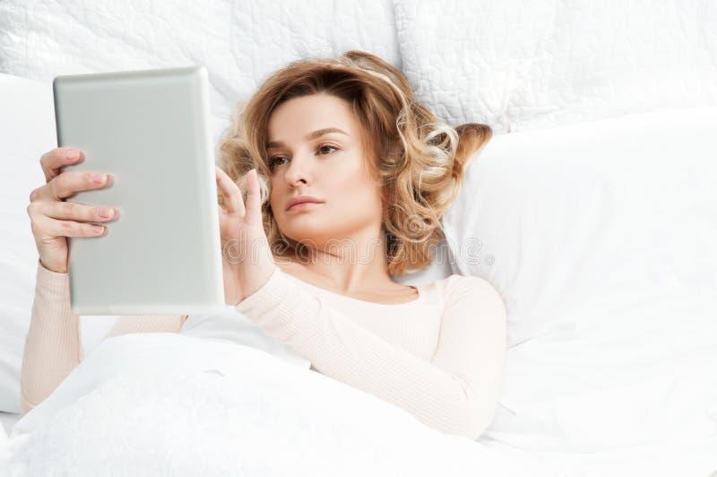 Όμορφη γυναίκα με την ταμπλέτα στο κρεβάτι στοκ φωτογραφία με δικαίωμα ελεύθερης χρήσης