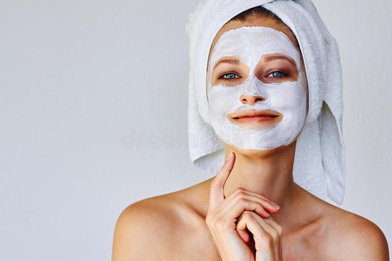 Όμορφη γυναίκα με την του προσώπου μάσκα στο πρόσωπό της Φροντίδα δέρματος και επεξεργασία, SPA, φυσικές ομορφιά και cosmetology  στοκ εικόνες