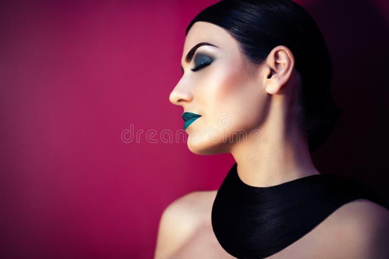 Όμορφη γυναίκα με την τυρκουάζ σύνθεση και το μοντέρνο hairstyle στοκ εικόνα