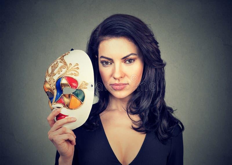 Όμορφη γυναίκα με τη ζωηρόχρωμη μάσκα καρναβαλιού στοκ εικόνα