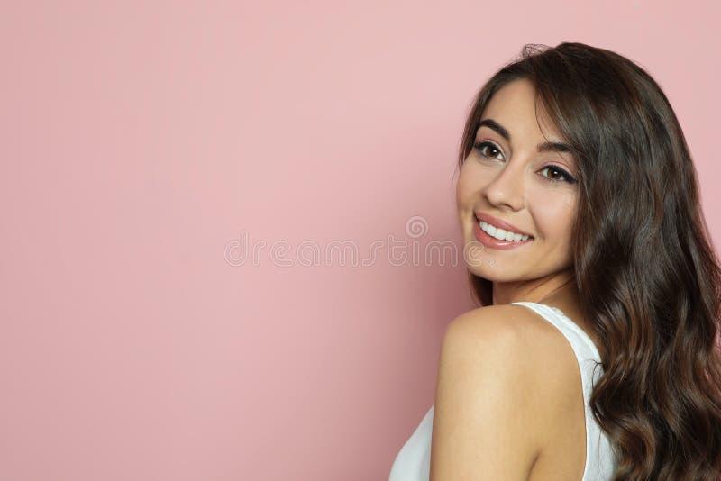 Όμορφη γυναίκα με τη λαμπρή κυματιστή τρίχα στο υπόβαθρο χρώματος στοκ εικόνες με δικαίωμα ελεύθερης χρήσης