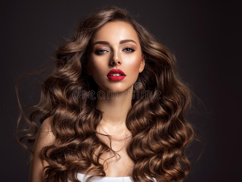 Όμορφη γυναίκα με τη μακριά καφετιά τρίχα και το κόκκινο κραγιόν στοκ φωτογραφία
