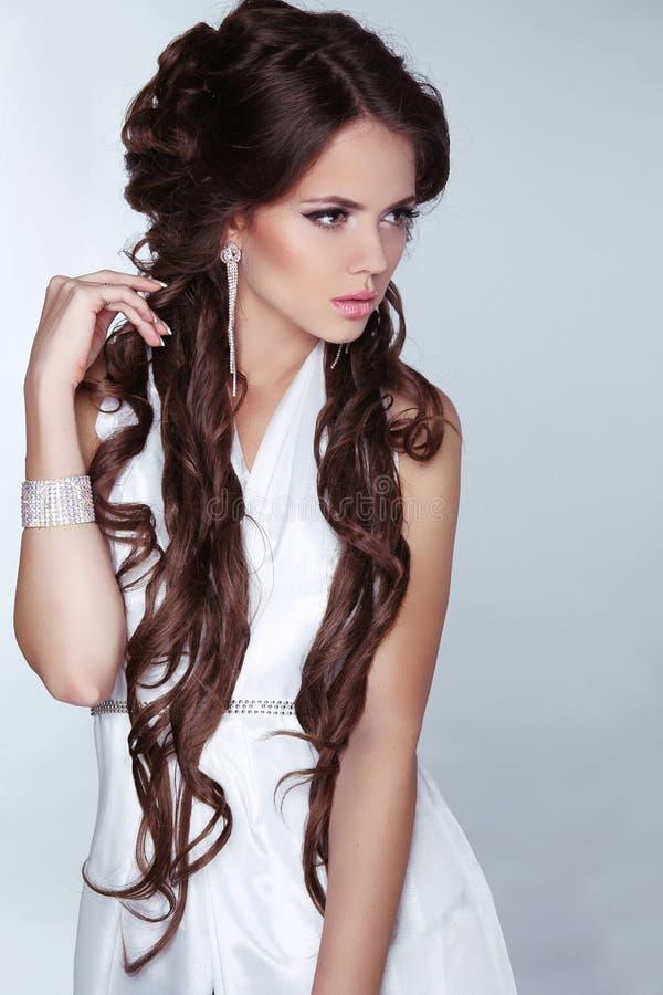 Όμορφη γυναίκα με τη μακριά καφετιά τρίχα που φορά στο άσπρο isol φορεμάτων στοκ φωτογραφία