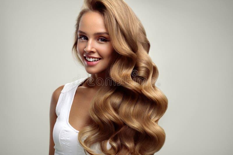 _ Όμορφη γυναίκα με τη μακριά ξανθή σγουρή τρίχα hairstyle στοκ εικόνες