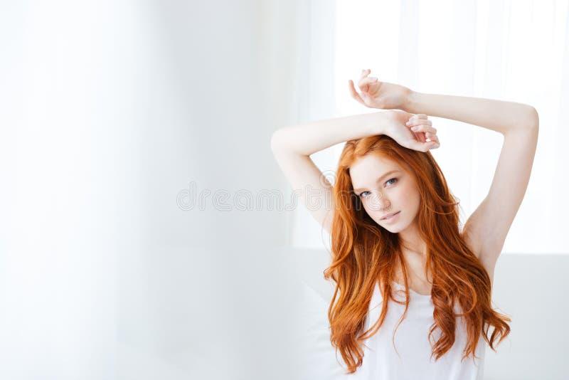 Όμορφη γυναίκα με τη μακροχρόνια κόκκινη συνεδρίαση τρίχας στο κρεβάτι στοκ φωτογραφία με δικαίωμα ελεύθερης χρήσης