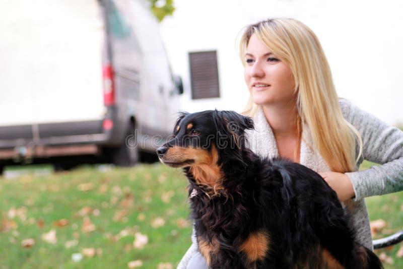 Όμορφη γυναίκα με τη μικρή μικτή συνεδρίαση και την τοποθέτηση σκυλιών φυλής του μπροστά από τη κάμερα στον ξύλινο πάγκο στο πάρκ στοκ εικόνες με δικαίωμα ελεύθερης χρήσης
