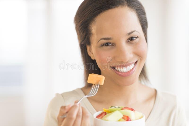 Όμορφη γυναίκα με τη σαλάτα φρούτων στο σπίτι στοκ φωτογραφία