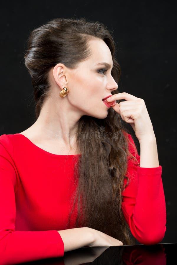 Όμορφη γυναίκα με τη σκοτεινή τρίχα και το βράδυ makeup κόκκινος προκλητικός φορεμάτων στοκ φωτογραφίες