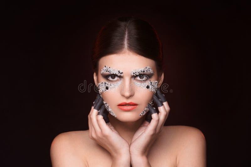 Όμορφη γυναίκα με τη συντήρηση κρυστάλλων makeup τα χέρια της κοντά στο πρόσωπο στοκ φωτογραφία με δικαίωμα ελεύθερης χρήσης