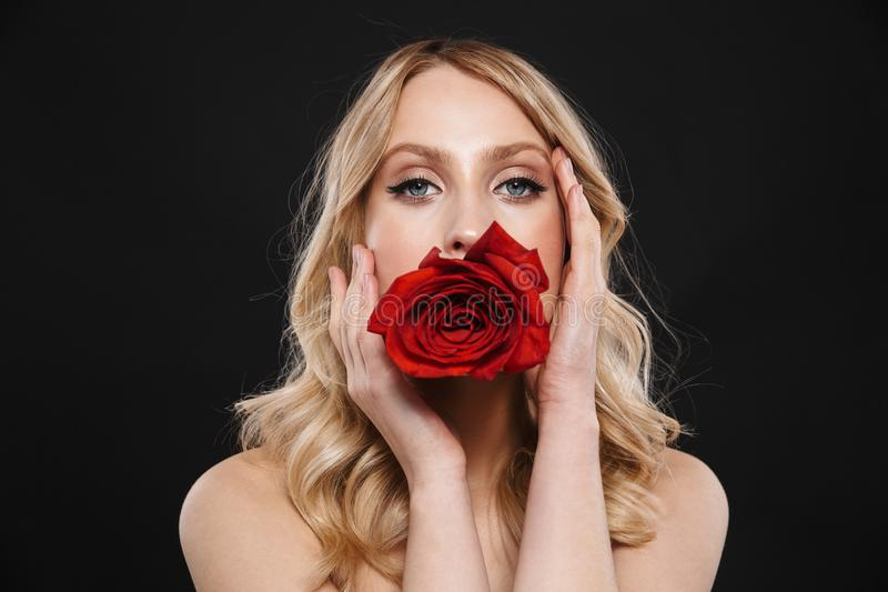 Όμορφη γυναίκα με τη φωτεινή κόκκινη χειλική τοποθέτηση makeup που απομονώνεται πέρα από το μαύρο υπόβαθρο με το λουλούδι στοκ εικόνες