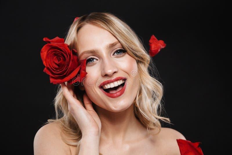 Όμορφη γυναίκα με τη φωτεινή κόκκινη χειλική τοποθέτηση makeup που απομονώνεται πέρα από το μαύρο υπόβαθρο με το λουλούδι στοκ φωτογραφίες