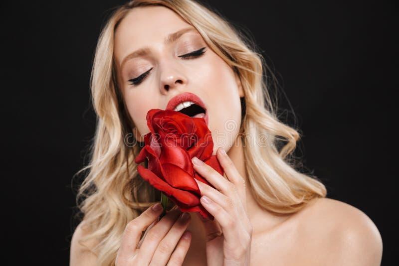 Όμορφη γυναίκα με τη φωτεινή κόκκινη χειλική τοποθέτηση makeup που απομονώνεται πέρα από το μαύρο υπόβαθρο με το λουλούδι στοκ εικόνα με δικαίωμα ελεύθερης χρήσης