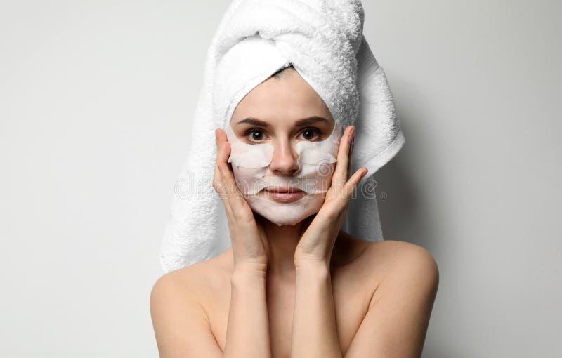 Όμορφη γυναίκα με τις μάσκες προσώπου και ματιών βαμβακιού στοκ φωτογραφία με δικαίωμα ελεύθερης χρήσης