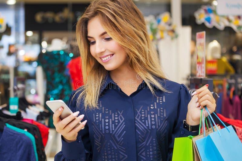 Όμορφη γυναίκα με τις τσάντες αγορών που εξετάζει το τηλέφωνό της στοκ εικόνες
