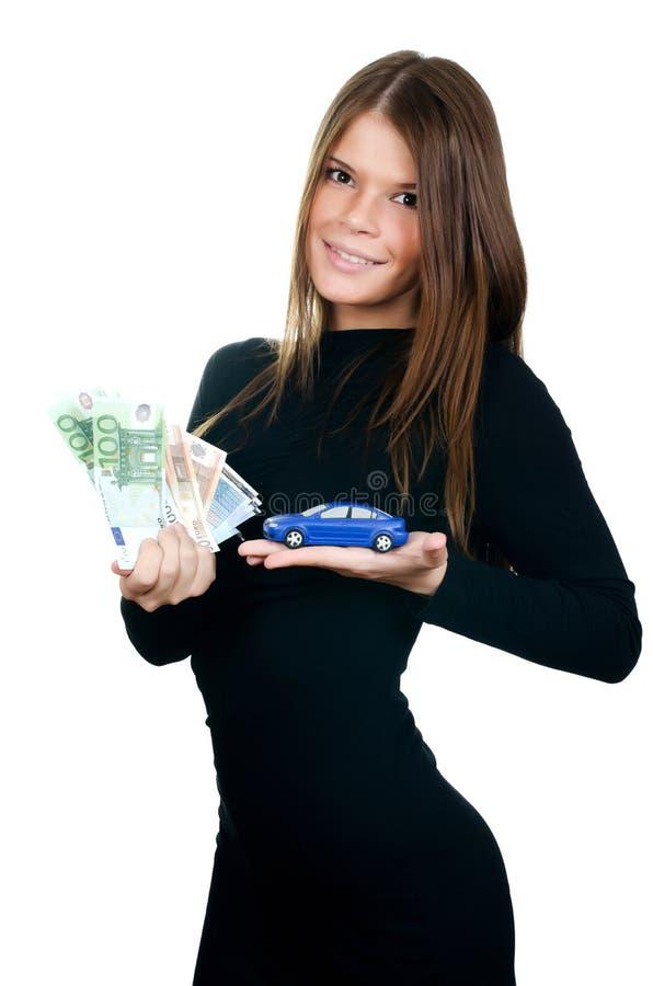 Όμορφη γυναίκα με το αυτοκίνητο χρημάτων και παιχνιδιών στα χέρια στοκ φωτογραφία