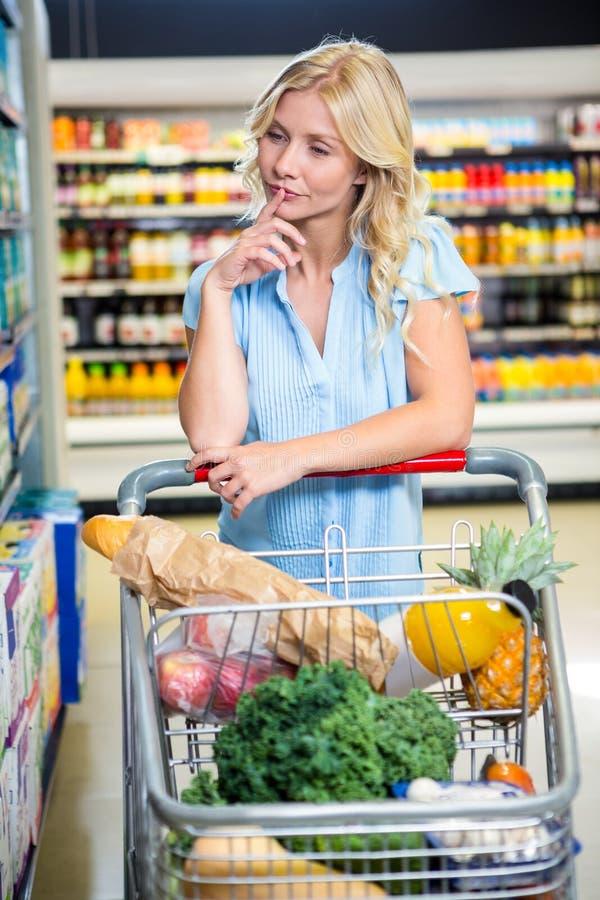 Όμορφη γυναίκα με το κάρρο που επιλέγει το προϊόν στοκ εικόνα
