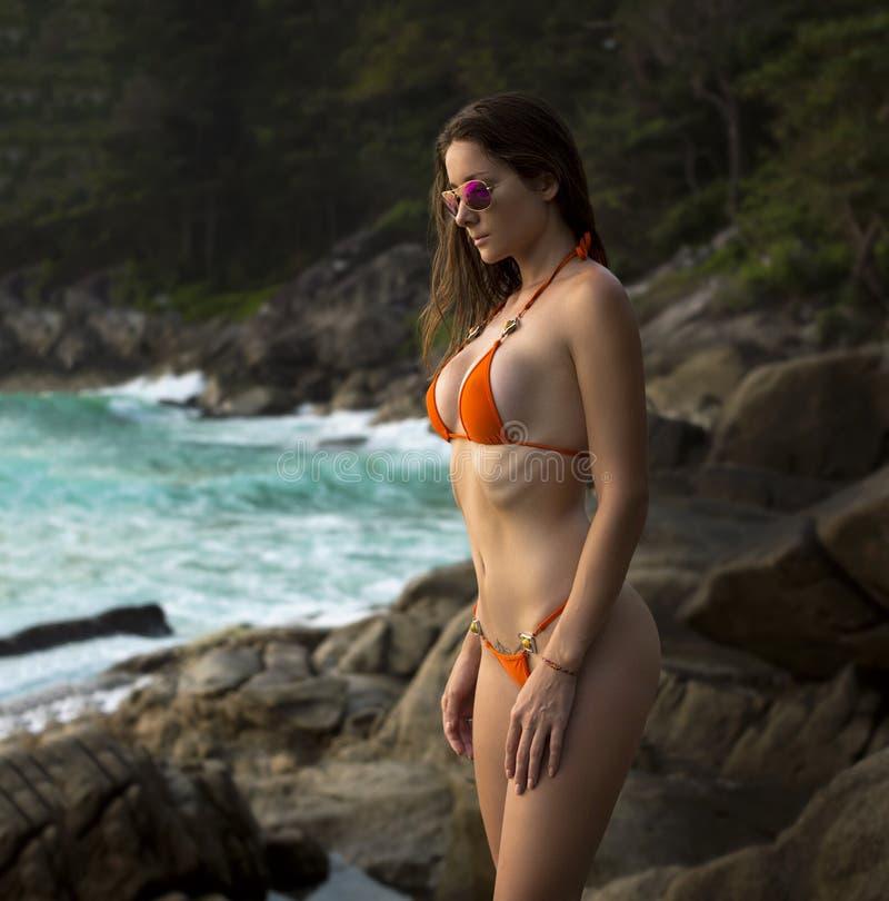 Όμορφη γυναίκα με το κατάλληλο σώμα στο προκλητικό μπικίνι, τροπικός απότομος βράχος στοκ φωτογραφίες