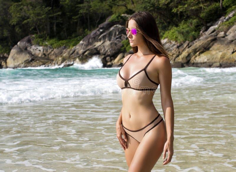 Όμορφη γυναίκα με το κατάλληλο σώμα στο προκλητικό μπικίνι, τροπικός απότομος βράχος στοκ φωτογραφία