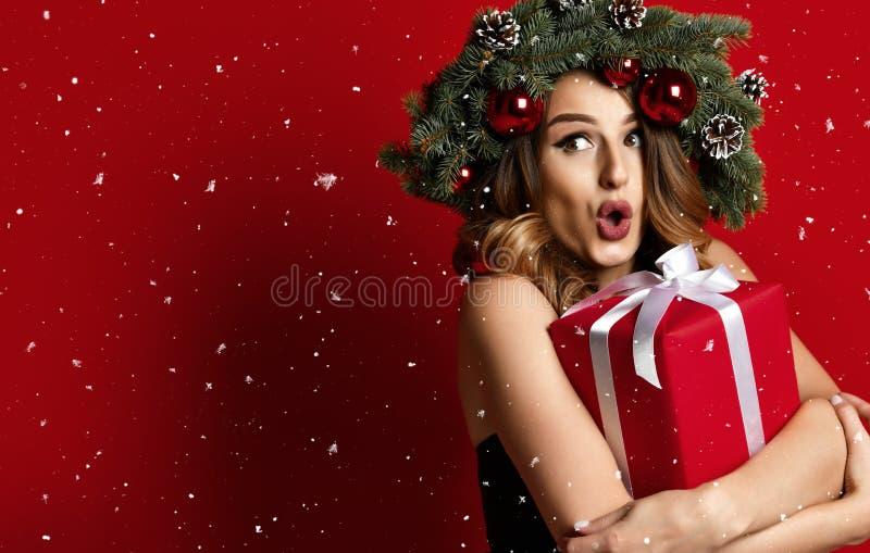 Όμορφη γυναίκα με το κομψό στεφάνι έλατου Χριστουγέννων με τους κώνους και τη νέα έκπληξη κιβωτίων δώρων έτους παρόντες στοκ εικόνες
