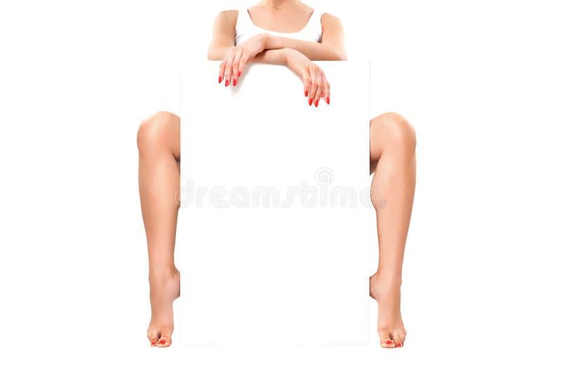 Όμορφη γυναίκα με το κόκκινο μανικιούρ και το καλά-καλλωπισμένο δέρμα, που κάθονται με το έμβλημα στοκ φωτογραφία