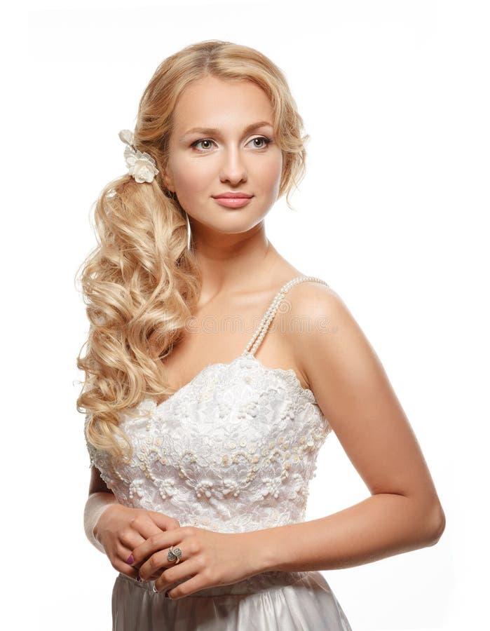 Όμορφη γυναίκα με το μακρυμάλλες φορώντας πολυτελές γαμήλιο φόρεμα στοκ φωτογραφία