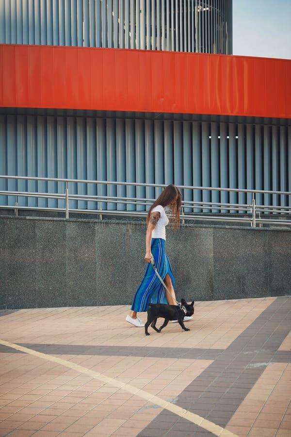Όμορφη γυναίκα με το μαύρο γαλλικό κουτάβι μπουλντόγκ στην οδό στοκ φωτογραφία