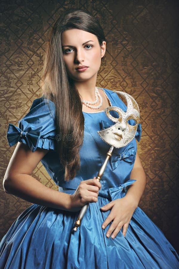Όμορφη γυναίκα με το μπλε φόρεμα και την ενετική μάσκα στοκ εικόνα