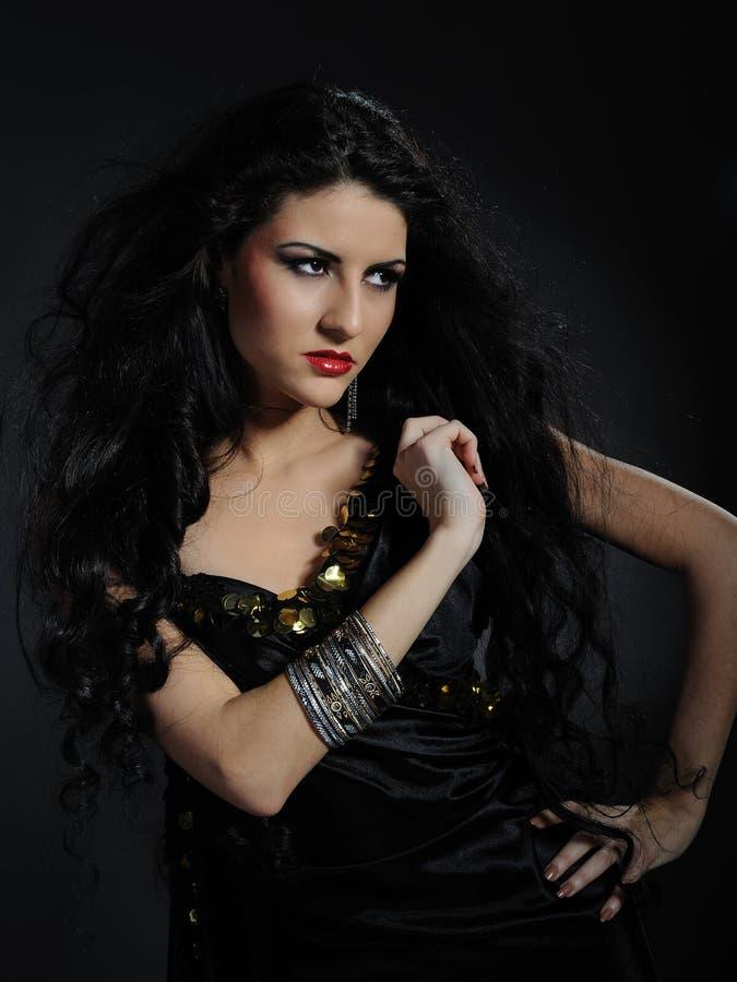 Όμορφη γυναίκα με το πολύ μαύρο υγιές τρίχωμα στοκ εικόνα με δικαίωμα ελεύθερης χρήσης