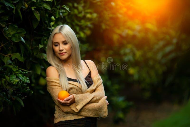Όμορφη γυναίκα με το πορτοκάλι στον οπωρώνα στοκ φωτογραφία με δικαίωμα ελεύθερης χρήσης