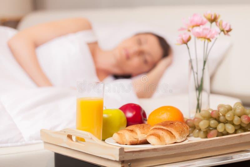 Όμορφη γυναίκα με το πρόγευμα στο κρεβάτι νωρίς στοκ εικόνα